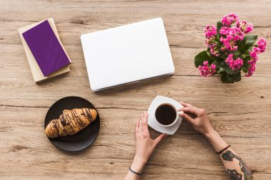 cropped shot of woman with cup of coffee at tabletop with laptop, books and croissant on plate