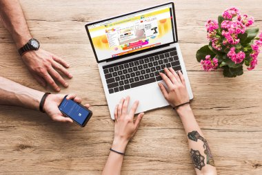 cropped shot of man with smartphone with facebook logo in hand and woman at tabletop with laptop with aliexpress website and kalanchoe flower
