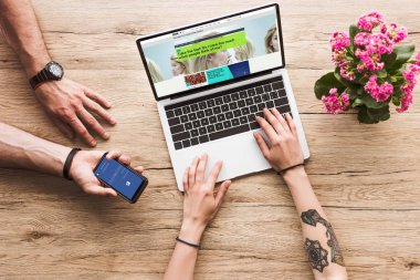 cropped shot of man with smartphone with facebook logo in hand and woman at tabletop with laptop with bbc website and kalanchoe flower