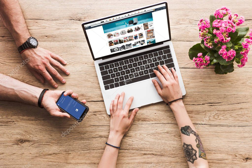 cropped shot of man with smartphone with facebook logo in hand and woman at tabletop with laptop with amazon website and kalanchoe flower