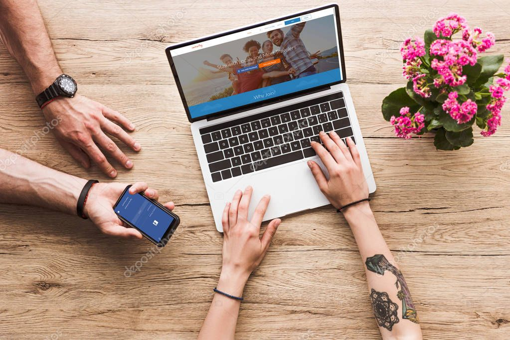 cropped shot of man with smartphone with facebook logo in hand and woman at tabletop with laptop with couchsurfing website and kalanchoe flower