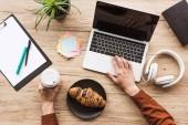 oříznutý obraz člověka pracuje u stolu s notebookem, sluchátka, učebnice, schránky, zaúčtujte ji, květináči, šálek kávy a croissantu