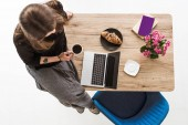 Fotografie top view of woman with cup of coffee sitting on table with croissant, laptop, flowers, book and textbook