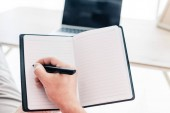ořízne obraz muže, který psal v učebnici u stolu s notebookem