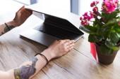 levágott lövés a tetovált nő nyitó laptop asztalhoz a pot virágok