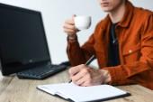 Fényképek részleges kilátás nyílik ember kávét iszik, és írásban tankönyv asztalhoz a számítógép és számítógép-billentyűzet