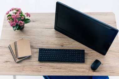 top view of computer monitor with blank screen, textbooks, flowers, computer keyboard and mouse on table