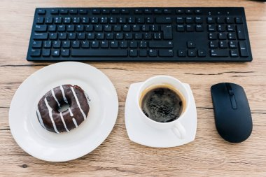 top view of doughnut, coffee cup, computer mouse and computer keyboard on wooden table