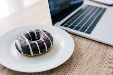 closeup view of doughnut on plate and laptop with blank screen on wooden table