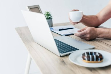 partial view of man holding cup of coffee at table with laptop, textbook, photo frame, potted plant and doughnut on plate