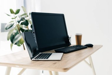 front view of workplace with laptop, computer, paper cup of coffee on table and potted plant