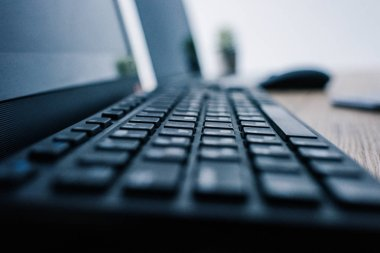 close up view of computer keyboard at table with computer mouse and laptop on blurred background