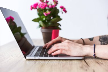 cropped shot of tattooed woman typing on laptop at table with flowers