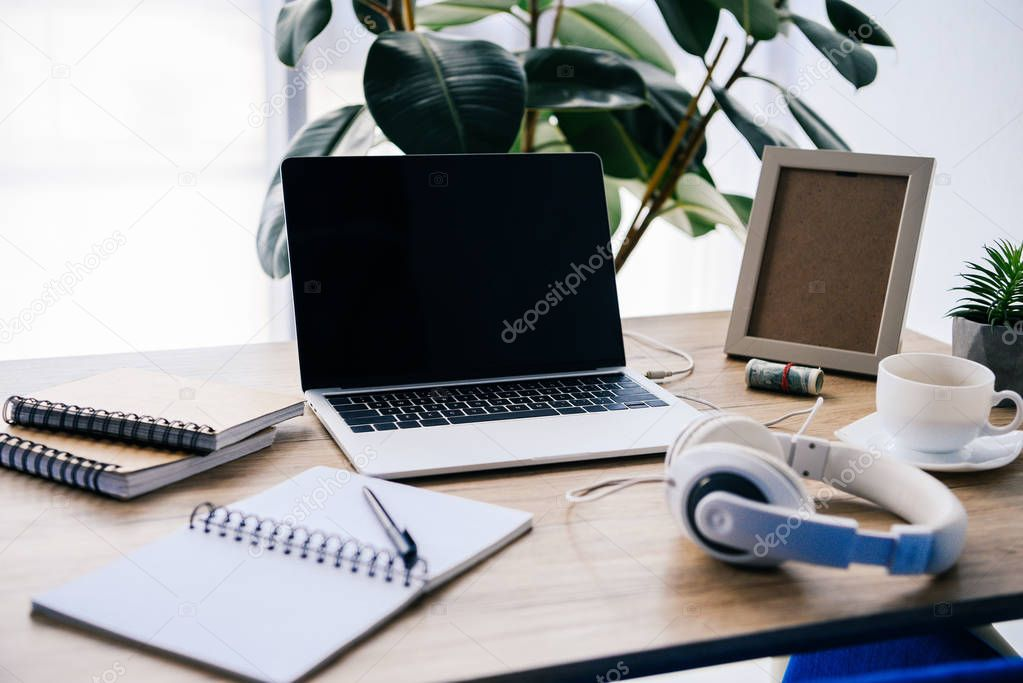 closeup view of laptop with blank screen at table with headphones, textbooks, coffee cup, photo frame, potted plant and roll of cash money