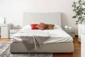 interiér moderní lehké ložnice s barevnými polštáři na bílé posteli