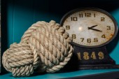 Fotografie old vintage clock and two different thread balls on wooden shelf in room