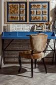 Interieur eines modernen Wohnzimmers im Retro-Stil mit blauem Tisch, Stuhl und Fotos in Rahmen