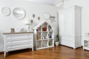 interior of modern light bedroom with white shelves and cupboard