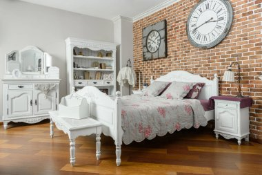 interior of modern light bedroom with clocks on wall and wooden furniture
