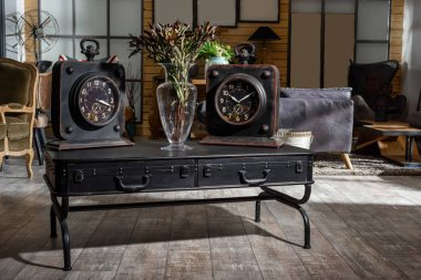 interior of modern retro styled living room with two clocks and dried flowers on wooden black table