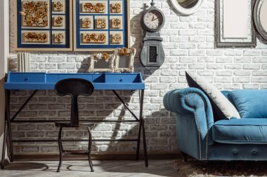 interior of modern retro styled living room with chair, table, sofa and clock on wall