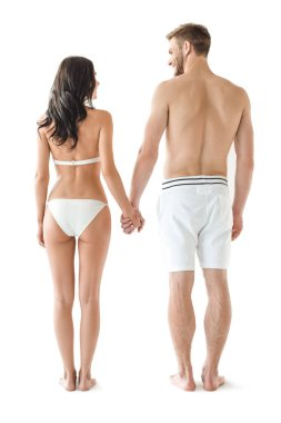 rear view of young cheerful couple in swimwear holding hands, isolated on white