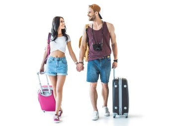 Young travelers with travel bags holding hands and looking at each other, isolated on white stock vector