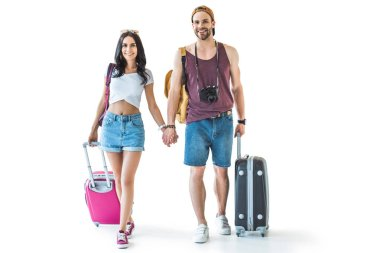 couple of young tourists with baggage holding hands together, isolated on white