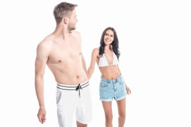 young smiling couple in swimwear holding hands, isolated on white