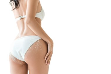 cropped view of woman showing buttocks in white bikini with sand, isolated on white