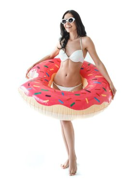 smiling woman in bikini and sunglasses holding inflatable donut, isolated on white