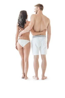 back view of beautiful couple in swimwear hugging isolated on white