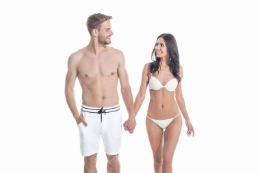young couple in swimwear holding hands and looking at each other, isolated on white