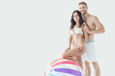 beautiful couple in swimwear posing with beach ball, isolated on white