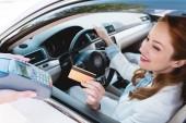 Lächelnde Geschäftsfrau im Auto, die mit Kreditkarte bezahlt