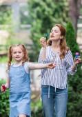 Fotografie Porträt von Mutter und Tochter Seifenblasen im park