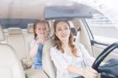Fotografie portrét usmívající se žena, která řídila auto a dceru ukazující daleko na sedadla cestujících