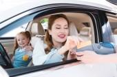 Lächelnde Geschäftsfrau bezahlt mit Kreditkarte für Take-away-Bestellung im Auto