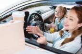 Fotografie Selektivní fokus usměvavá podnikatelka s odvézt objednávku s dcerou na sedadle cestující v autě