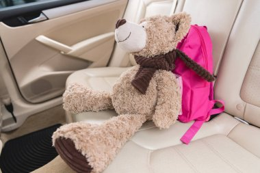 close up view of teddy bear with pink backpack on seat in car