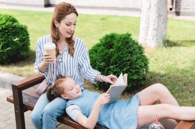 smiling kid reading book with mother near by while resting on bench together on street
