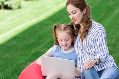 portrait of mother and daughter using laptop while resting on bag chair together