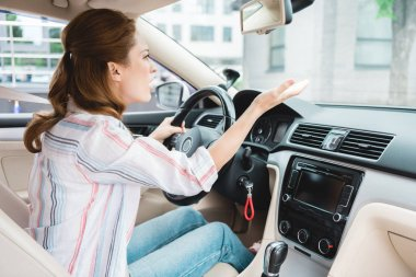 side view of emotional woman gesturing while driving car