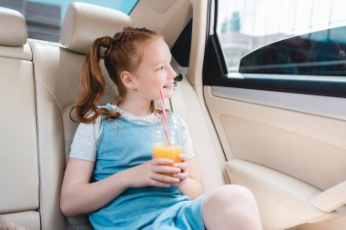 cheerful kid with juice looking out car window while sitting in car