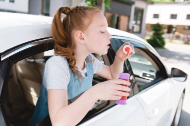 side view of child blowing soap bubbles while sitting in car