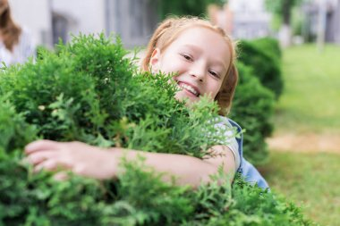 portrait of cheerful child hugging green bush