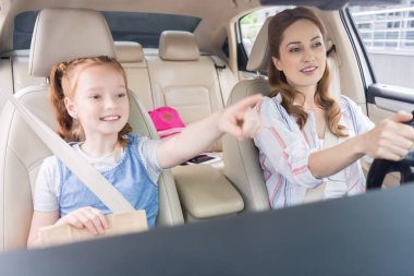 portrait of smiling woman driving car and daughter pointing away on passengers seat