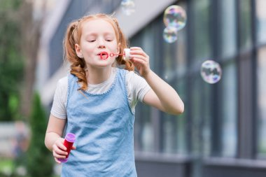 portrait of cute child blowing soap bubbles on street