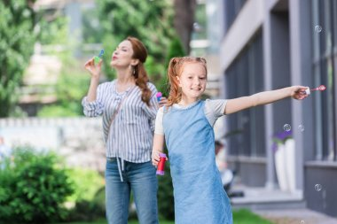 mother and smiling daughter blowing soap bubbles in park