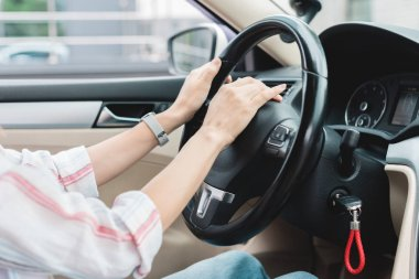 partial view of woman honking horn while driving car